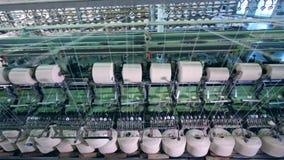Fiber som köas på spolar på en textilfabrik lager videofilmer