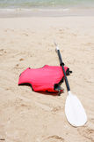 Fiberglass blade and red life-jacket on the beach Stock Photo