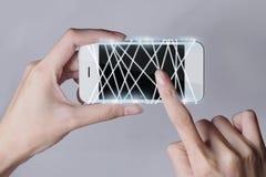 Fibra óptica que emite la luz blanca con smartphone y las manos Imagen de archivo libre de regalías