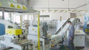A fibra de vidro entra na máquina de corte e o trabalhador verifica partes na correia transportadora filme