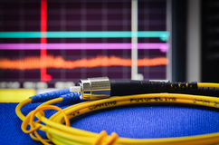 Fibre optic cable with spectrum analiser in the background Stock Image