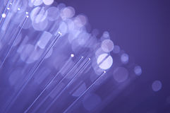 Fibre optic lights. A close up of illuminated fibre optic clear light strands against a lavender background Stock Photo