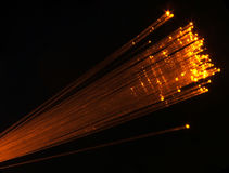 Fibre optics. Orange fibre optic cables diagonally cross image (up stock image