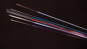 Fibres optiques de code à couleurs vives sur le fond foncé Images stock