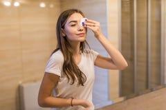 Ficar fresco e limpa Jovem mulher bonita que toca em sua cara com esponja e que sorri ao estar na frente do espelho fotografia de stock