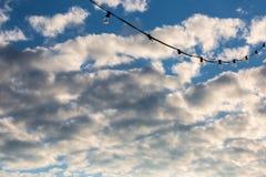 Ficelle de lampe accrochant sur un fond nuageux de ciel bleu Photo libre de droits