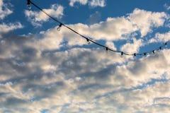 Ficelle de lampe accrochant sur un fond nuageux de ciel bleu Photographie stock libre de droits