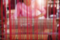 Ficelle en soie rouge avec l'humain de tache floue avec la machine de tissage Photos libres de droits