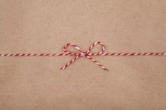 Ficelle ou ficelle de Noël attachée dans un arc sur le fond de papier d'emballage photographie stock libre de droits