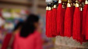 Ficelles rouges de bonne chance de Buddist avec des achats de dame à l'arrière-plan Image stock