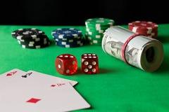 Fichas de póker, dados, naipes y torcido 100 billetes de banco en el th imagen de archivo