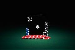 Fichas de póker en la tabla con pares de tarjetas negras Fotos de archivo