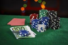 Fichas de póker, euros y tarjetas en la tabla fotos de archivo libres de regalías