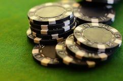 Fichas de póker negras en el fieltro del verde Foto de archivo
