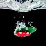 Fichas de póker que caen en el agua clara fotografía de archivo