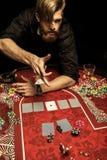 Fichas de póker que lanzan del hombre barbudo en la tabla mientras que juega el póker Imagen de archivo