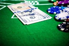 Fichas de póker y billetes de banco en la tabla fotos de archivo