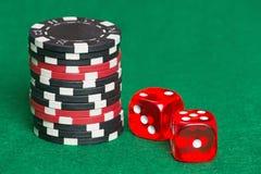 Fichas de póker y dados rojos y negros en un fieltro verde del casino Fotos de archivo libres de regalías