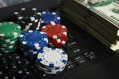 Fichas de póker y paquetes de dólares en un ordenador portátil fotografía de archivo libre de regalías