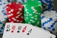Fichas de póker y tarjetas que muestran la casa llena con 10 y el as en cierre para arriba Fotografía de archivo libre de regalías