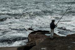 Ficherman na skałach morzem, obraz stock