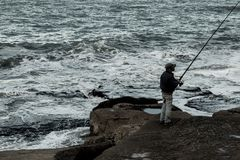 Ficherman op de rotsen, door het overzees stock afbeelding