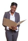 Fichero africano de risa de la lectura de la mujer de negocios Fotos de archivo