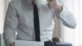 Fichero del caso del cliente de la lectura del abogado en la oficina, taza de consumición del hombre de negocios del café metrajes