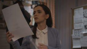 Fichero detective femenino de la declaración del testigo que analiza en la oficina, atento leyendo metrajes