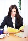 Ficheros sorprendidos de la lectura de la mujer de negocios Foto de archivo