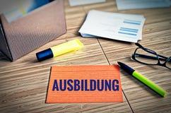 Fiches avec des thèmes légaux avec les verres, le stylo et le bambou avec le mot allemand Ausbildung dans l'éducation anglaise image libre de droits
