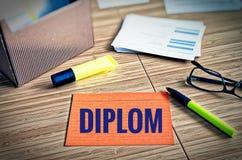 Fiches avec des thèmes légaux avec les verres, le stylo et le bambou avec le mot allemand Diplom en diplôme anglais photos libres de droits