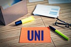 Fiches avec des thèmes légaux avec les verres, le stylo et le bambou avec le mot allemand UNI à l'université anglaise images stock