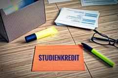 Fiches avec des thèmes légaux avec des verres, stylo et bambou et le mot allemand Studienkredit dans le prêt anglais d'étude photo stock