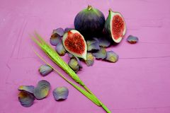 Fichi dolci maturi, frutta con la metà e quarto su fondo rosa Fotografia Stock