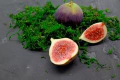 Fichi dolci maturi, frutta con la metà e quarto su fondo scuro Fotografia Stock