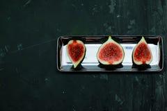 Fichi dolci maturi, frutta con la metà e quarto su fondo scuro Fotografie Stock Libere da Diritti