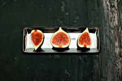 Fichi dolci maturi, frutta con la metà e quarto su fondo scuro Immagini Stock