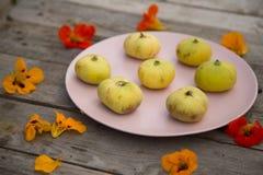 Fichi giallo pallidi su un piatto rosa su un piano d'appoggio di legno fotografia stock