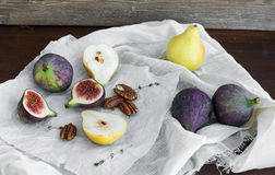 Fichi, pere e dadi pekan su un tessuto bianco Fotografia Stock Libera da Diritti