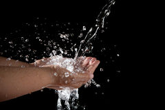 Fichier de la main et de l'eau pleuvante à torrents éclaboussant sur le fond noir Image stock