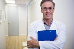 Fichier de recopie de dentiste tout en se tenant au lobby dans la clinique dentaire images stock