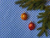 Fichtenzweige mit Weihnachtsbaum spielt in Form von Nüssen auf einem Hintergrund des Stoffes in den Tupfen Lizenzfreies Stockbild