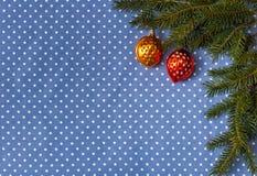 Fichtenzweige mit Weihnachtsbaum spielt in Form von Nüssen auf einem Hintergrund des Stoffes in den Tupfen Stockfoto