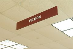 Fiction sign. A sign hanging from a library ceiling indicates the fiction section Stock Photo