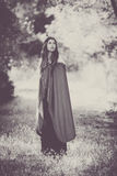 Fiction woman in cloak in forest. Cosplay fiction woman in cloak in forest Stock Images