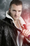 Fictional character - handsome warrior. Handsome warrior holding a saber over a cloudy background Royalty Free Stock Photo