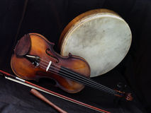 Fiddle & Bodhran 1. A violin, bodhran and stick (beater), are together on a black cloth background. The fiddle and bodhran are traditional folk instruments Stock Photo