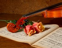 Fiddle and roses. Vintage still life with a violin, music book and soft roses Royalty Free Stock Photography
