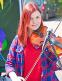 Fiddler at Highland Games. Young woman musician playing the fiddle  at Inverness Highland Games  held on 20th July 2013 Royalty Free Stock Images